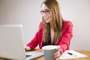 Woman searching for cheaper car insurance on laptop