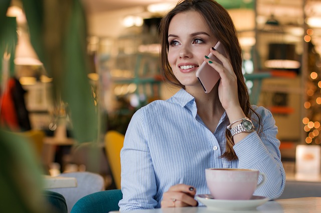 Smiling woman on telephone with a coffee